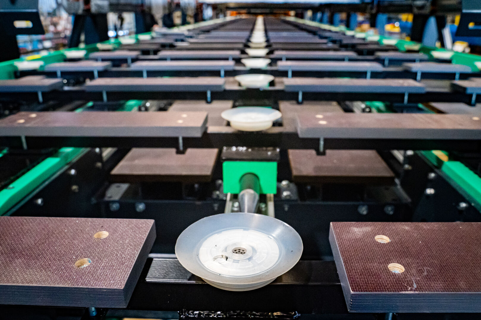 Suction cup conveyor transfers panels steady from scanning to repair stations resulting ability to handle warped panels and minimal need to reject warped panels.