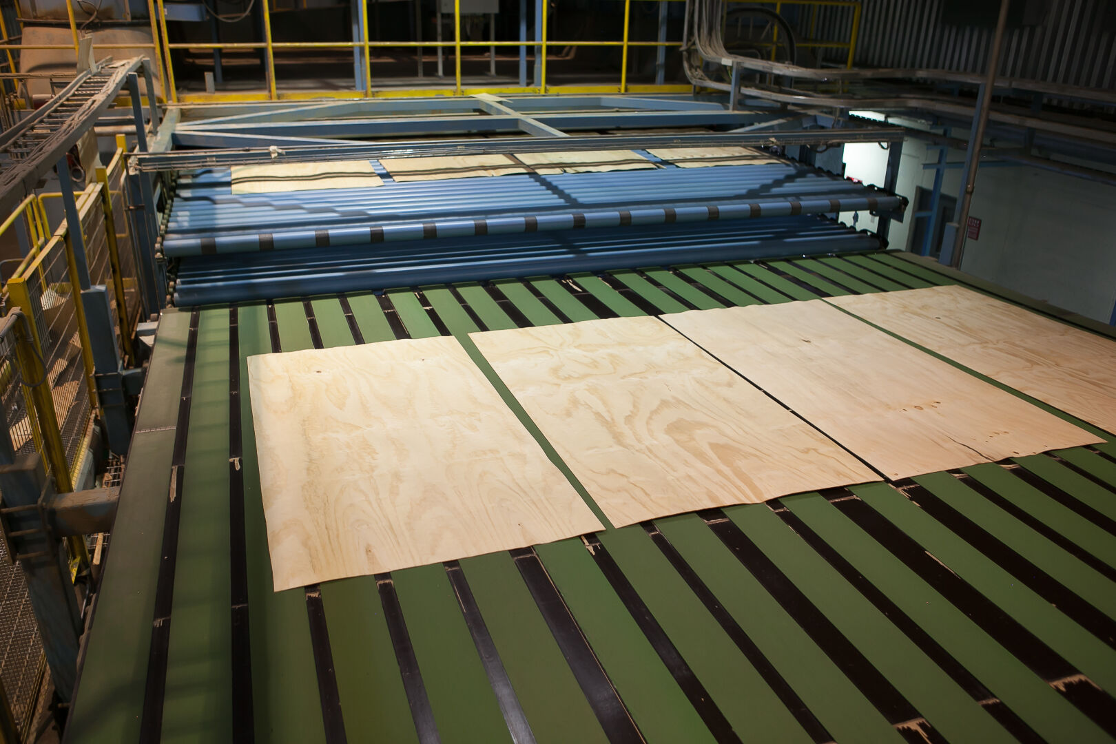 Crossing station of the dryer guides the veneer sheets to one conveyor leading to grading and sorting line.