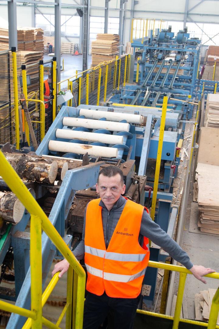 Раймондс Спулс-Вилканс (Raimonds Spuls-Vilcans), член совета директоров компании AmberBirch, на фоне линии лущения шпона серииR3